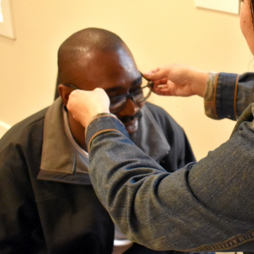 Image of adult man trying on glasses.